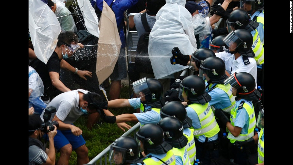 "<strong>September 28:</strong> Riot police use pepper spray as they clash with pro-democracy protesters outside the government headquarters in Hong Kong. <a href=""http://www.cnn.com/2014/09/22/asia/gallery/hong-kong-students-protest/index.html"">Demonstrations began</a> in response to China's decision to allow only Beijing-vetted candidates to stand in the city's 2017 election for chief executive. Protesters say Beijing has gone back on its pledge to allow universal suffrage in Hong Kong, which was promised ""a high degree of autonomy"" when it was handed back to China by Britain in 1997. The umbrella has become the defining image of the protest movement, used to shield protesters from tear gas and the elements."