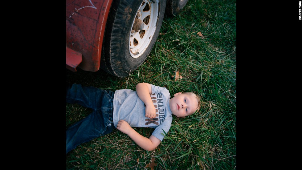 "Caleb Patterson, 4, rests beneath a flatbed trailer during a church picnic held near Plato, Missouri, in 2012. Plato is the ""mean center of population"" for the United States. That means, according to the U.S. Census Bureau, it's the place ""where an imaginary, flat, weightless and rigid map of the United States would balance perfectly if all residents were of identical weight."""