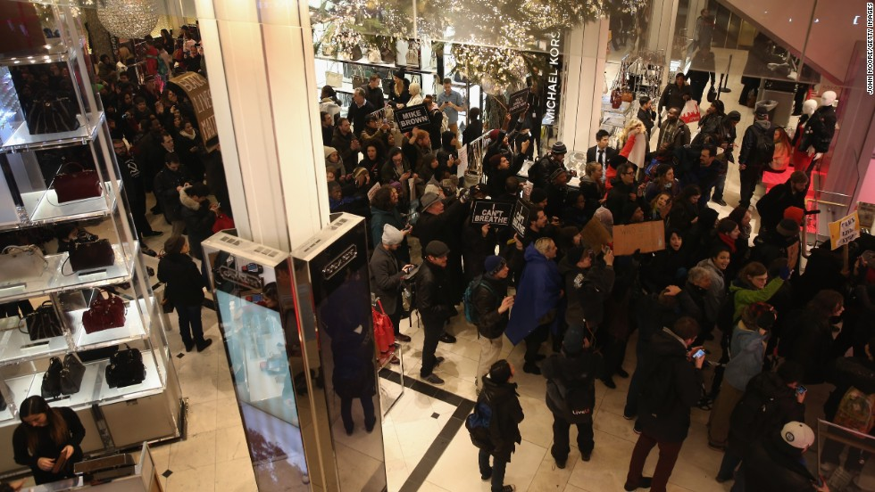 "Demonstrators march through a Macy's in Manhattan before staging a ""die-in"" at the iconic department store on December 5."