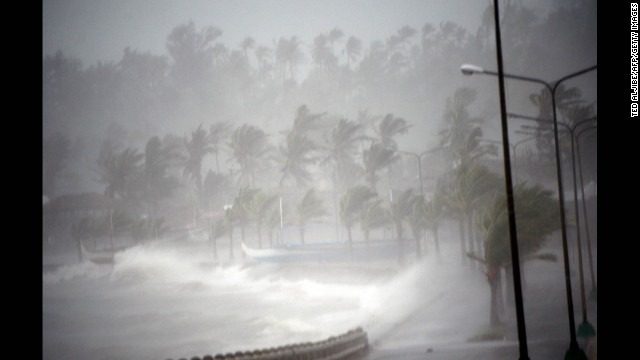 Strong winds and rain pound the seawall hours before Typhoon Hagupit passes near the city of Legazpi on December 7, 2014.  Typhoon Hagupit tore apart homes and sent waves crashing through coastal communities across the eastern Philippines, creating more misery for millions following a barrage of deadly disasters.      AFP PHOTO/TED ALJIBE        (Photo credit should read TED ALJIBE/AFP/Getty Images)