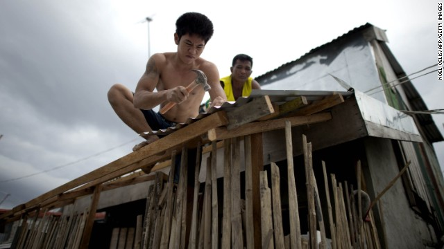 Workers reinforce the roof of a house in Manila on December 7.
