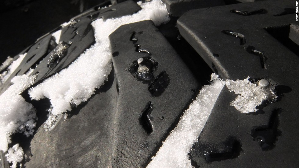 Driving up the side of a snow-covered volcano requires enormous tires equipped with metal studs.