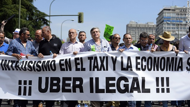 """(FILES) A file picture taken on June 11, 2014 shows taxi drivers carrying a banner during a strike action in protest of unliscensed taxi-type-services in central Madrid. A judge on December 9, 2014 banned the popular US cellphone-based taxi service Uber from operating in Spain, court officials said, following similar attempted moves in several other countries. Drivers hired for rides via the application """"lack the administrative authorisation to carry out the job, and the activity they carry out constitutes unfair competition, """" the court services said. AFP PHOTO / GERARD JULIENGERARD JULIEN/AFP/Getty Images"""
