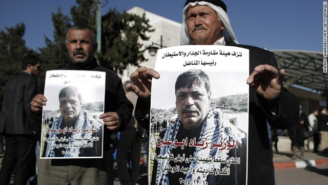 Palestinian men carry posters bearing the portrait of Palestinian Cabinet member Ziad Abu Ain, after the announcment of his death outside the main hospital in the West Bank city of Ramallah on December 10, 2014.