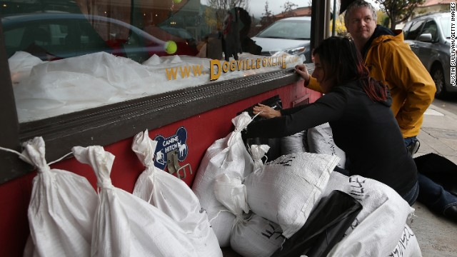 SAN ANSELMO, CA - DECEMBER 10:  Staysea Colteaux (L) and Chris Furbee (R) set up sandbags and seal a vent in front of Dogville on December 10, 2014 in San Anselmo, California. The San Francisco Bay Area is bracing for a severe storm that is expected to bring high winds and heavy rain that could topple trees and cause widespread flooding. Urban areas could see up to 6 inches of rain in less than 24 hours.  (Photo by Justin Sullivan/Getty Images)