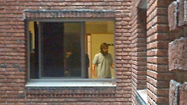 "One of the six Guantanamo inmates transferred to Uruguay and who are expected to leave in freedom after more than a decade in what one called the ""black hole"" of the US military prison, is seen through a window of the Military Hospital in Montevideo, on December 8, 2014. The men, who arrived in Uruguay Sunday on refugee status after 12 years of detention without charge, are undergoing medical exams at the hospital. Uruguayan President Jose Mujica had announced in March that the South American country would take in the inmates on ""humanitarian grounds, "" in a bid to help his US counterpart Barack Obama fulfill his long-delayed promise to close the prison set up in the wake of the 9/11 attacks. AFP PHOTO / STR --- ALTERNATIVE CROP--/AFP/Getty Images"