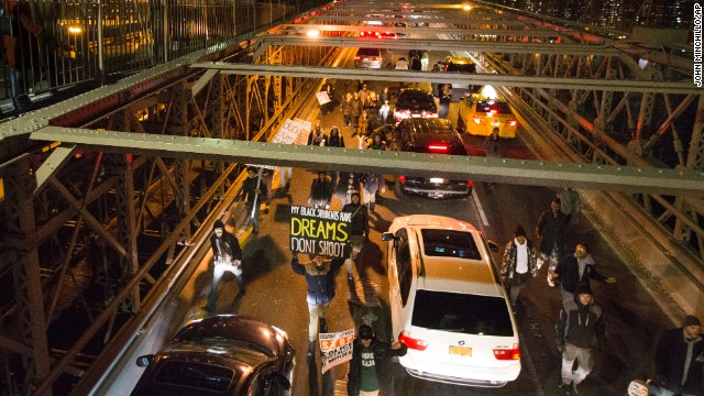 Demonstrators march over the inbound lane of the Brooklyn Bridge in New York, Saturday, December 13.
