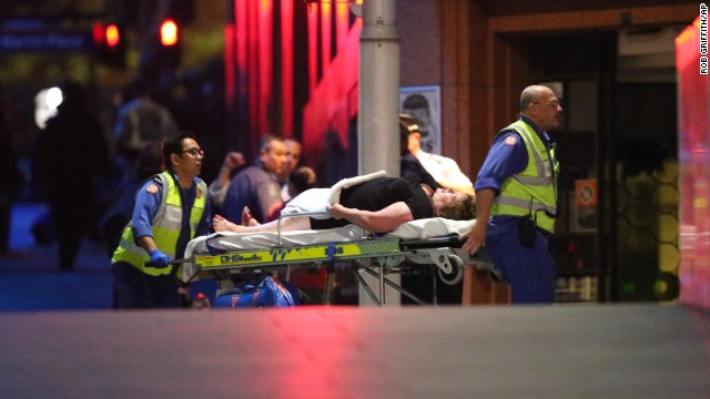A injured hostage is wheeled to an ambulance after shots were fired during  a cafe  siege at Martin Place in the central business district of Sydney, Australia, Tuesday, Dec. 16, 2014. New South Wales state police would not say what was happening inside the cafe or whether hostages were being held. But television footage shot through the cafe's windows showed several people with their arms in the air.(AP Photo/Rob Griffith)