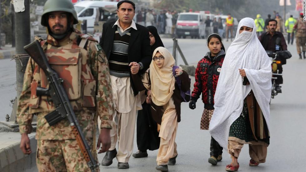 Parents escort their children away from the school.