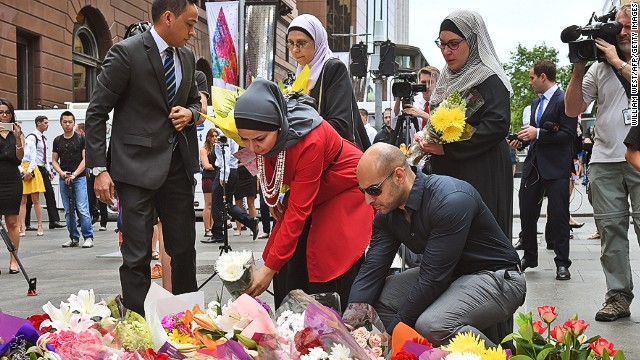 Representatives of the Muslim community lay flowers at a floral memorial at the scene of a dramatic siege which left two hostages dead, expressing shock and grief that something like this could happen in their easy-going city, in Sydney on December 16, 2014. Two hostages and an extremist Iranian-born gunman were killed in a siege that ended when armed police stormed a central Sydney cafe, as a shocked Australia struggled to come to terms with the tragedy. AFP PHOTO/William WEST (Photo credit should read WILLIAM WEST/AFP/Getty Images)