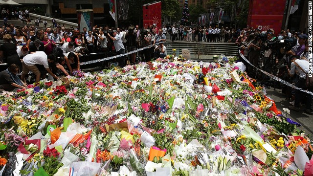 SYDNEY, AUSTRALIA - DECEMBER 16: Flowers are left as a sign of respect at Martin Place on December 16, 2014 in Sydney, Australia. The siege in Sydney's Lindt Cafe in Martin Place is over after 16 hours. Police raided the cafe just after 2am AEDT on Tuesday morning. Three people have been confirmed killed, two hostages and the gunman. (Photo by Mark Metcalfe/Getty Images)