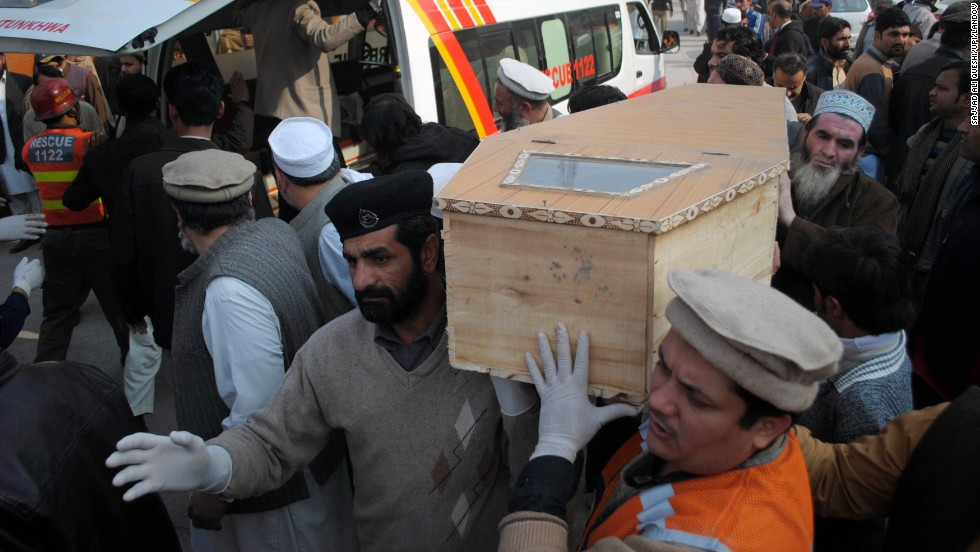 A victim's coffin is carried from an ambulance.