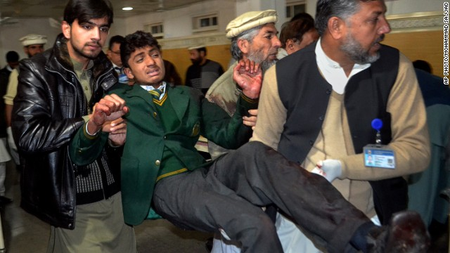 Pakistani volunteers carry a student injured in the shootout at a school under attack by Taliban gunmen, at a local hospital in Peshawar, Pakistan,Tuesday, Dec. 16, 2014. Taliban gunmen stormed a military school in the northwestern Pakistani city, killing and wounding dozens, officials said, in the latest militant violence to hit the already troubled region. (AP Photo/Mohammad Sajjad)