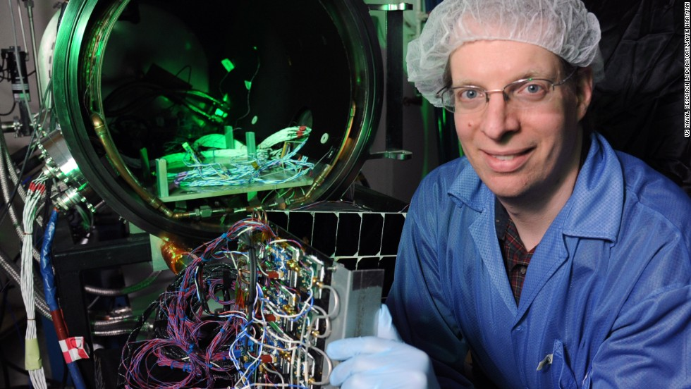 Dr Paul Jaffe of the US Naval Research Laboratory holds a module he designed for space solar power in front of a customized vacuum chamber used to test it.  He says that while space-based solar power is likely decades away, many countries, in particular Japan, are still pursuing research into the power source.