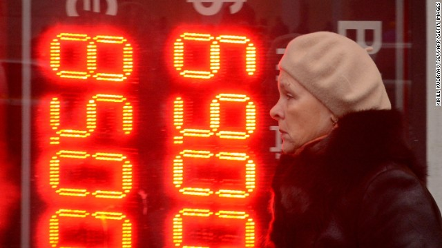 A woman walks past a board listing foreign currency rates against the Russian ruble outside an exchange office in central Moscow on December 16, 2014. The Russian ruble set a new all-time record low on Tuesday after bouncing back briefly despite an emergency move by Russia's central bank to raise interest rates to 17 percent. AFP PHOTO / KIRILL KUDRYAVTSEV (Photo credit should read KIRILL KUDRYAVTSEV/AFP/Getty Images