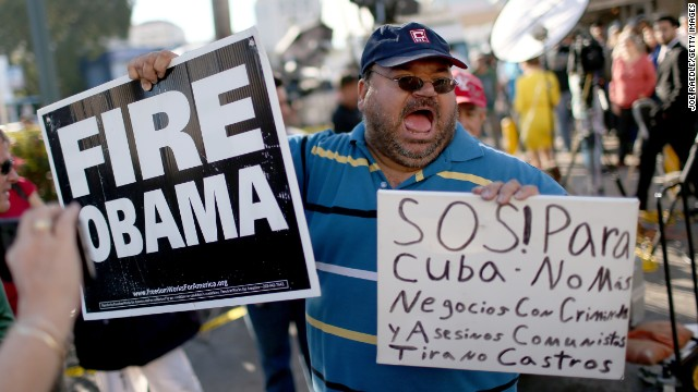 Caption:MIAMI, FL - DECEMBER 17: People stand outside the Little Havana restaurant Versailles, as they absorb the news that Alan Gross was released from a Cuban prison and that U.S. President Barack Obama wants to change the United States Cuba policy on December 17, 2014 in Miami, United States. Alan Gross, the American contractor had spent five years in Cuban jail. (Photo by Joe Raedle/Getty Images)