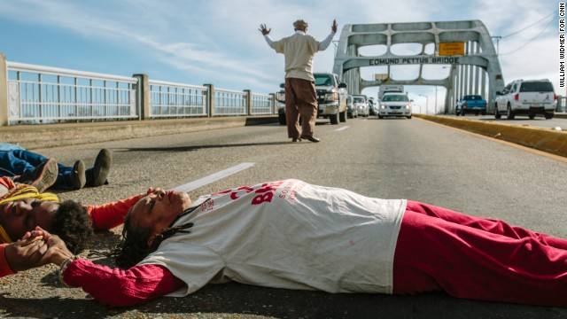 Selma, AL - 12/17/2014 - Faya Rose Toure (in white shirt) lay on the Edmund Pettus Bridge to block traffic.  A group of protestors led by Ms. Toure (also known as Rose Sanders) held a march in downtown Selma. The demonstration originated on the Edmund Pettus Bridge, where on March 7th, 1965, armed officers attacked peaceful civil rights demonstrators attempting to march to the state capital of Montgomery in an incident that became known as Bloody Sunday. The protestors marched to demand that video of a Selma police officer fatally shooting a 74-year-old man named Ananias Shaw be made public.