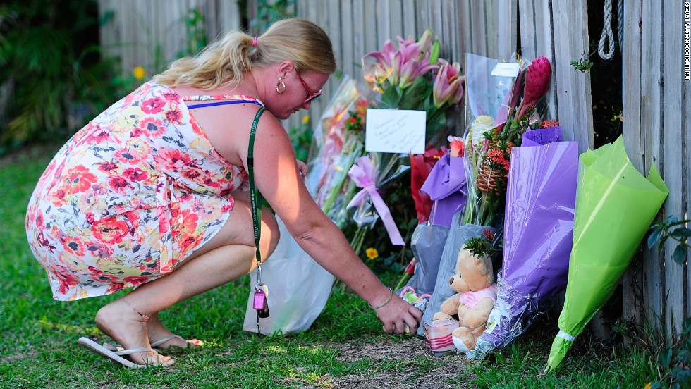 A woman lays flowers across the road from the crime scene.