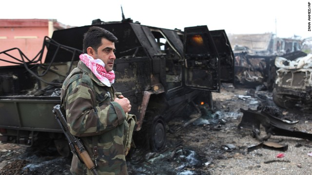 A member of the Kurdish forces stands next to an armored vehicle on December 18. The vehicle was destroyed by an improvised explosive device placed by ISIS militants that killed several Peshmerga fighters and injured dozens late Wednesday, as the Kurdish forces pushed towards Sinjar Mountain.