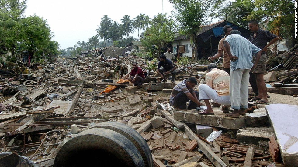 Sri Lankan men sort through debris of their destroyed homes in Galle on December 27, 2004.