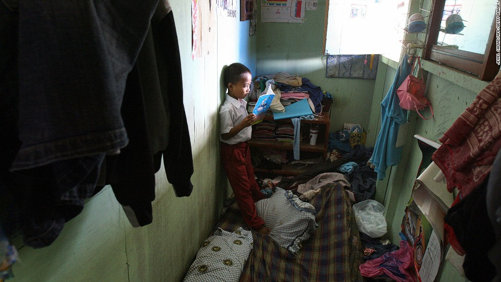 Tsunami victim Heru checks his homework inside his family's room at a temporary housing complex in Banda Aceh on December 12, 2006. Two years after the Indian Ocean tsunami wiped out their neighborhoods, many survivors struggled to understand why their homes have not been rebuilt.