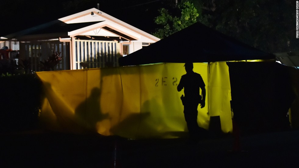 A police officer works at the scene where eight children were found dead in a suburban home in Cairns, Australia, on Friday, December 19.