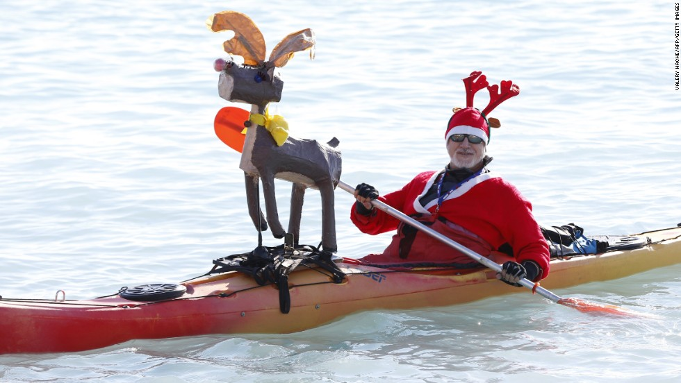 A man in a Santa outfit paddles a canoe decorated with a reindeer during the traditional Christmas bath in Nice, France, on Sunday, December 21.