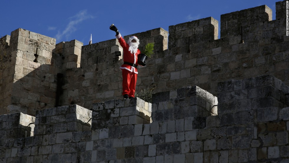 Santa waves to passers-by as he walks along Jerusalem's Old City walls on December 22.