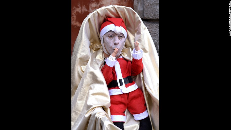 A street artist disguised as a little Santa in a cradle performs on December 22 in Rome.