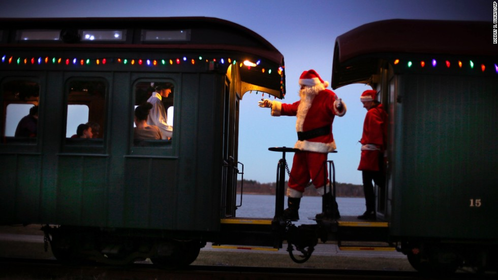 Santa greets passengers while moving between cars during the Polar Express train ride, a holiday fund-raiser, on Friday, December 19, at the Maine Narrow Gauge Railroad Co. and Museum in Portland.