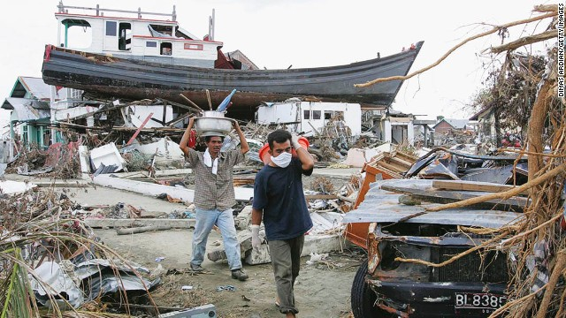 People displaced by the tsunamis, walk amid their ruined neighbourhood on January 4, 2005 in Banda Aceh, Indonesia. Indonesia, the country hardest hit by the Indian Ocean tsunami disaster, has lost over 94,000 people.