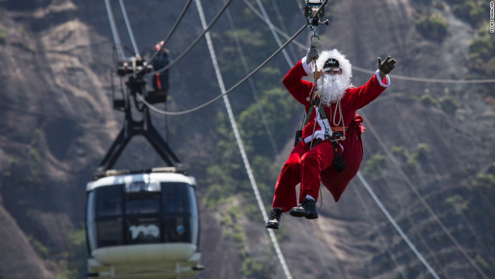 Santa takes a zip line away from Sugarloaf Mountain after riding on top of a cable car on Thursday, December 18, in Rio de Janeiro.