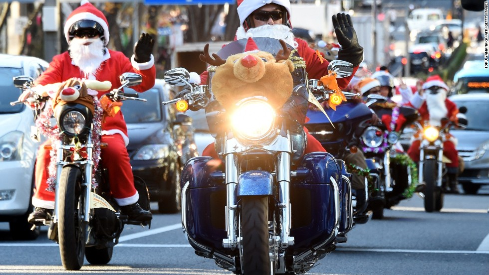 "Motorcyclists in Santa and reindeer outfits ride through the streets of Tokyo on December 23. The Christmas ""toy run"" by the Harley Santa Club is campaign against child abuse."