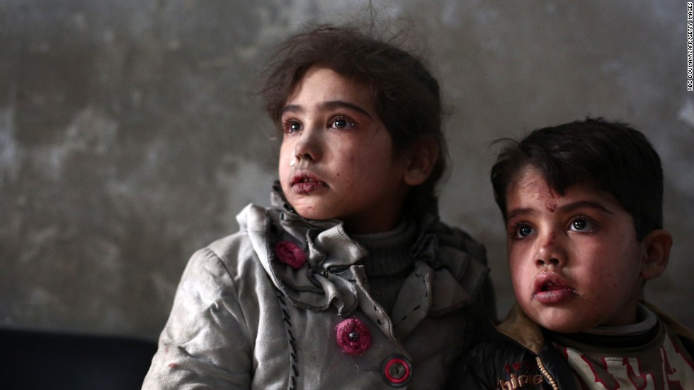 Syrian children await medical treatment at a makeshift clinic in the besieged rebel town of Douma, on Sunday, December 21, near Damascus.
