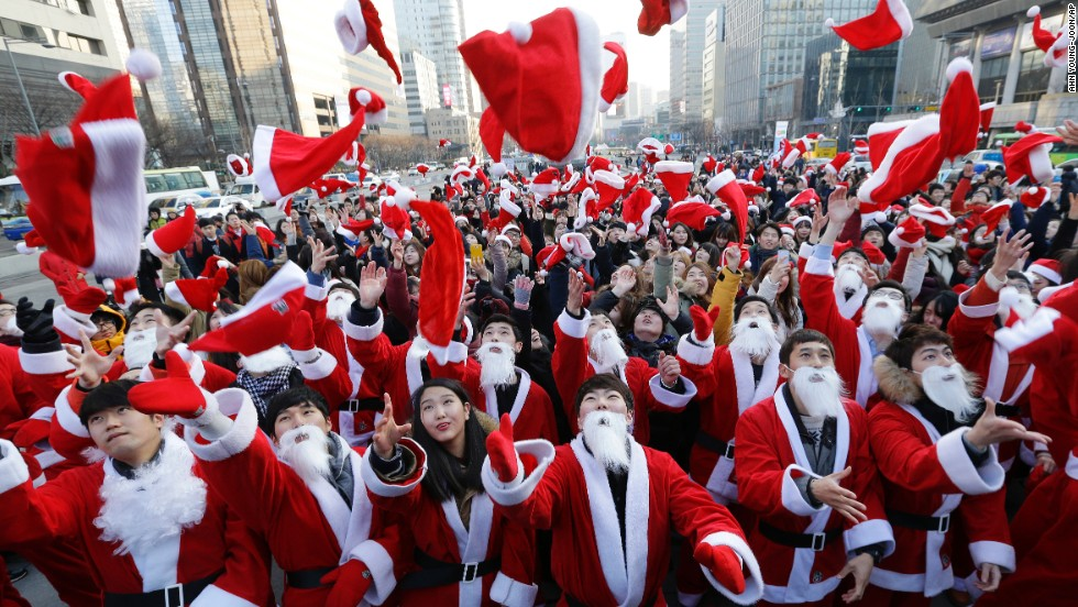 Volunteers in Santa outfits toss their hats into the air before delivering gifts to the poor on December 24 in Seoul, South Korea.