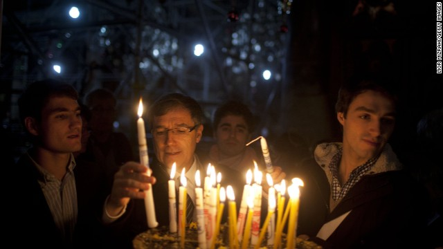 BETHLEHEM, WEST BANK - DECEMBER 24: Visitors light candles in the Church of the Nativity on December 24, 2014 in Bethlehem, West Bank. Every Christmas pilgrims travel to the church where a gold star embedded in the floor marks the spot where Jesus was believed to have been born. (Photo by Lior Mizrahi/Getty Images)