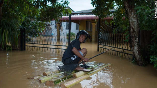 A man makes his way to his submerged house in Pengkalan Chepa, Malaysia, on Saturday.