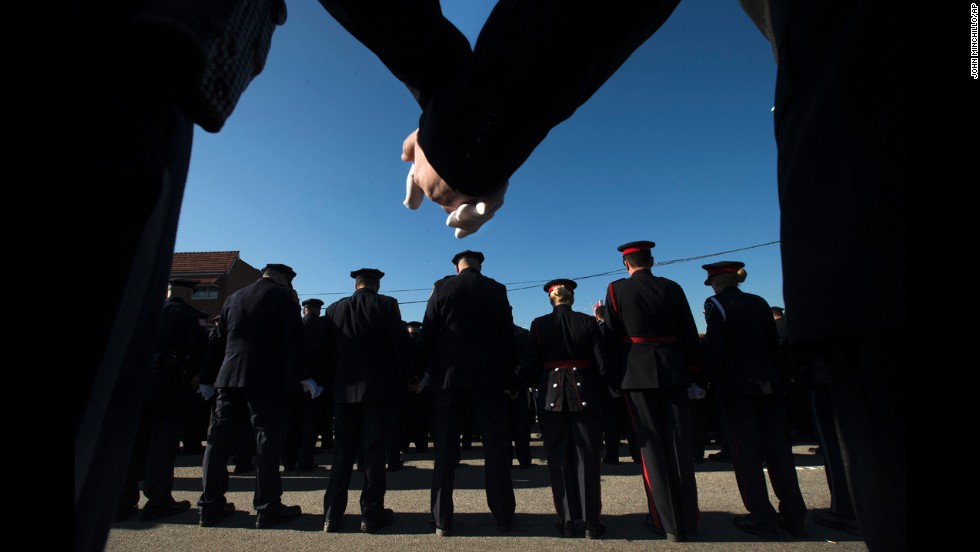 Police officers hold hands in prayer during the funeral services.