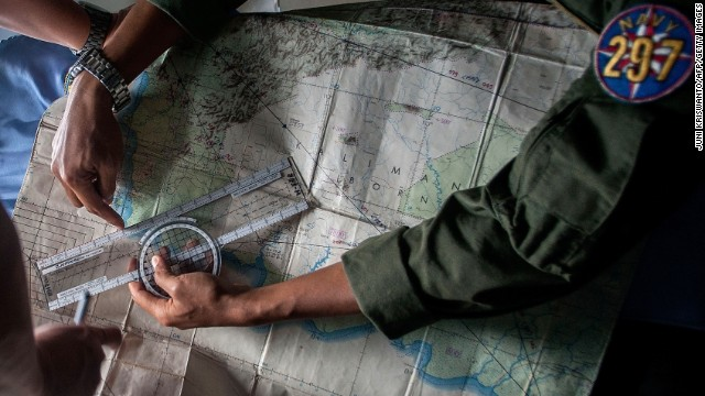 Indonesian Army personnel read a map during a search operation over the waters of the Java Sea on December 29.