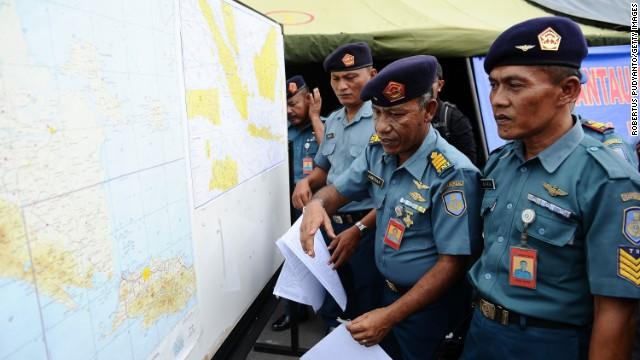 Indonesian naval officers prepare the operational air navigation map during the investigation of missing AirAsia flight QZ8501 outside the crisis center of Juanda International Airport Surabaya on December 29, 2014 in Surabaya, Indonesia.