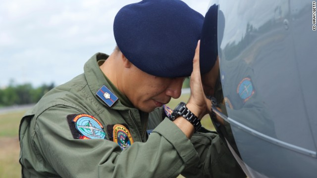 An Indonesian Navy airman prays on his plane before searching the waters near Bangka Island for debris from AirAsia Flight QZ8501 on December 30, 2014.