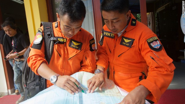 Indonesian Search and Rescue Helicopter pilots look over a map of the search area for debris from AirAsia Flight QZ8501 in the waters near Bangka Island, Indonesia on December 30, 2014.