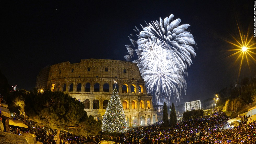 People cheer in front of Rome's ancient Colosseum.