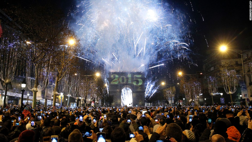 Revelers photograph fireworks over the Arc de Triomphe in Paris.