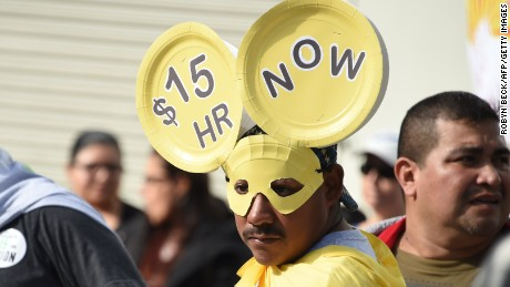 Fast food workers, healthcare workers and their supporters shout slogans at a rally and march in Los Angeles to demand an increase in the minimum wage to $15 per hour on December 4, 2014.