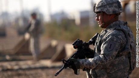 An American soldier stands guard at the Taji base complex which hosts Iraqi and US troops and is located thirty kilometres north of the capital Baghdad on December 29, 2014. Taji is one of an eventual five sites where the US and allied countries aim to train 5,000 Iraqi military personnel every six to eight weeks for combat against the Islamic State (IS) jihadist group.