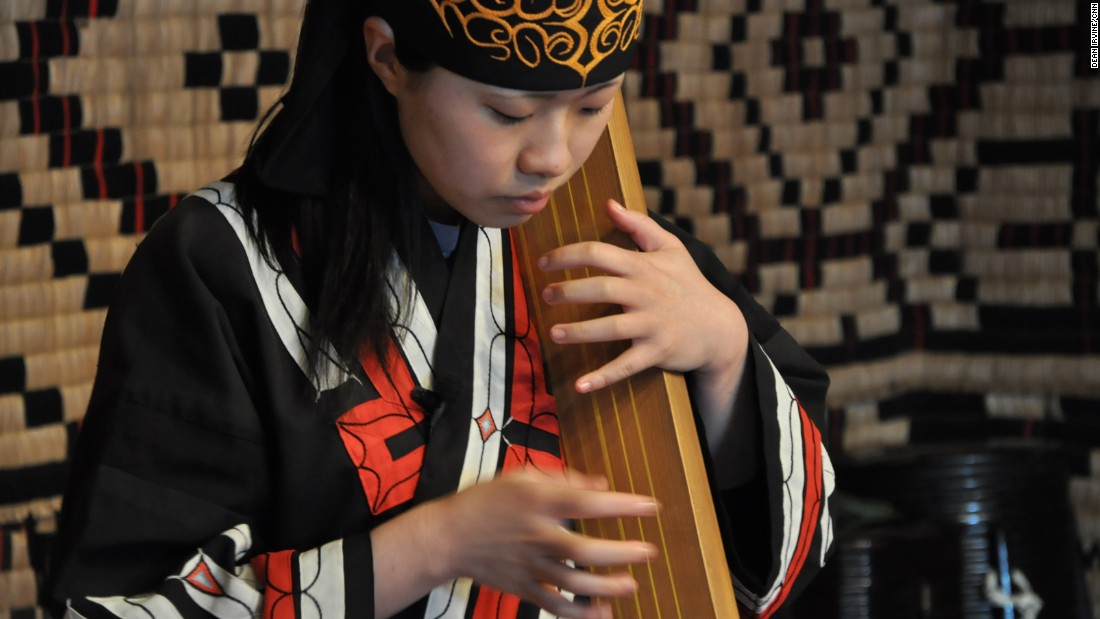 "A performer plays a traditional tonkori, a five-stringed instrument. Many of the place names in Hokkaido have a link to the Ainu language. The coastal town of Shiraoi where the Ainu Museum located means ""land of many horseflies.""  Sapporo is a derivation of the Ainu words for dry large river: ""sat poro pet."""