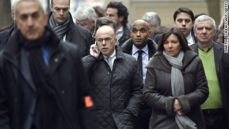 Caption:France's interior minister Bernard Cazeneuve (C, L) and Paris' Mayor Anne Hidalgo (C, R) arrive at the headquarters of the French satirical newspaper Charlie Hebdo in Paris on January 7, 2015, after armed gunmen stormed the offices leaving at least 11 people dead. AFP PHOTO / MARTIN BUREAU (Photo credit should read MARTIN BUREAU/AFP/Getty Images)