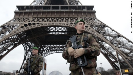 French soldiers patrol in front of the Eiffel Tower on January 7, 2015 in Paris as the capital was placed under the highest alert status after heavily armed gunmen shouting Islamist slogans stormed French satirical newspaper Charlie Hebdo and shot dead at least 12 people in the deadliest attack in France in four decades. Police launched a massive manhunt for the masked attackers who reportedly hijacked a car and sped off, running over a pedestrian and shooting at officers. AFP PHOTO / JOEL SAGET        (Photo credit should read JOEL SAGET/AFP/Getty Images)