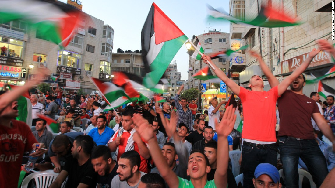 Palestinians celebrate in the West Bank city of Ramallah on May 30, 2014, after their team qualified for their maiden Asian Cup appearance with a 1-0 win over injury-hit Philippines in the final of the AFC Challenge Cup in Maldives.